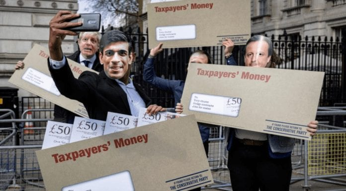 """Picture of the Week – Cesspit Street – Protestors brandishing envelopes of 'taxpayers' money' sum up the state of Boris Johnson's rotten government as ex-minister Johnny Mercer quite rightly brands it a """"cesspit"""""""
